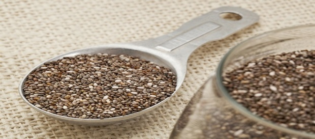 chia seeds in glass jar and on measuring aluminum tablespoon against burlap background, focus on the